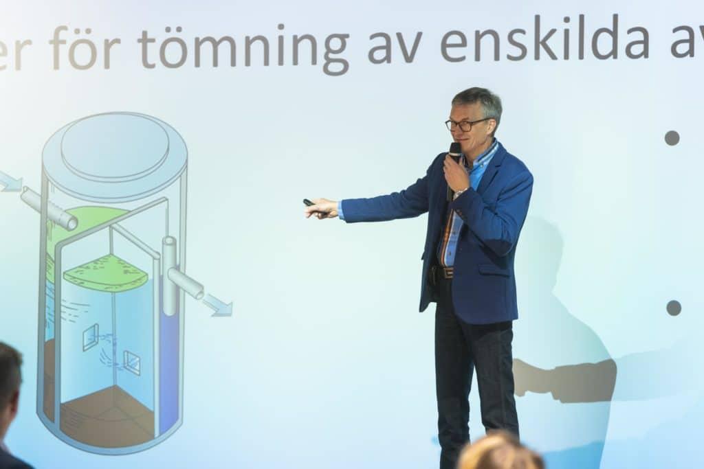 Kuvassa VA Process och Energigasin Jan-Olof Åström esittelee sakokaivon tyhjennysperiaatetta. Hänellä on toisessa kädessään mikrofoni, ja toisella kädellään hän viittaa valkokankaalla olevaan kuvaan kaivosta, joka on jaettu useaan lohkoon, jotka keräävät lietettä.