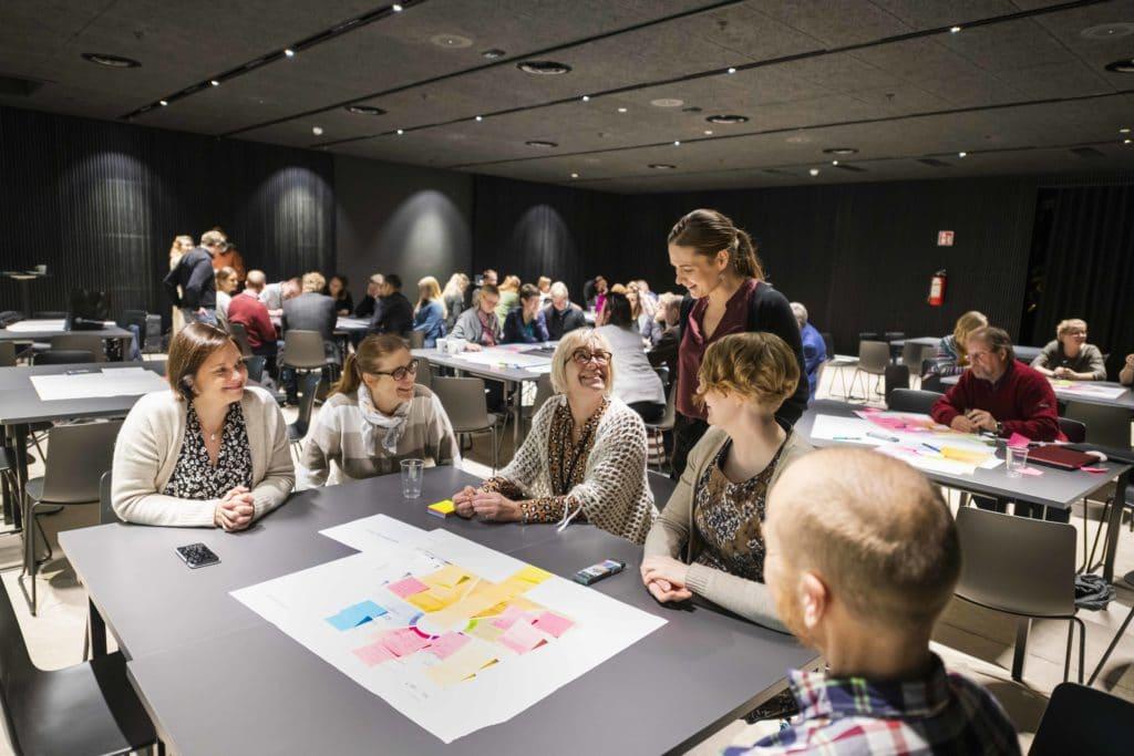 Kuvan etualalla pöydän ääressä istuu viisi ihmistä. Valonian haasteen vetäjä Riikka Leskinen seisoo pöydän keskivaiheilla. Ihmiset hymyilevät ja katsovat toisiaan keskustellessaan haasteesta.